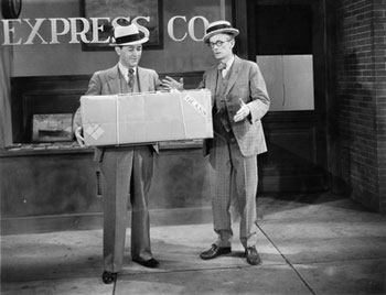 old fashioned black and white picture with 2 men and a package